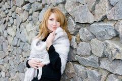 Menina com um xaile no fundo uma parede de pedra Foto de Stock
