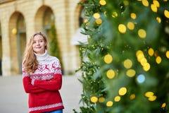 Menina com uma árvore de Natal brilhantemente decorada Imagem de Stock