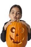 Menina com uma abóbora de Halloween Fotos de Stock