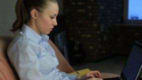 Menina com uma aparência bonita que senta-se no sofá que trabalha no computador video estoque