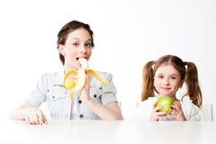 Menina com uma banana e uma maçã Foto de Stock Royalty Free