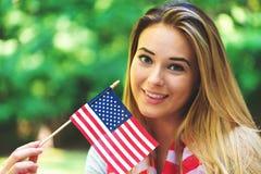 Menina com uma bandeira americana no quarto de julho Imagens de Stock