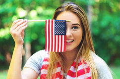 Menina com uma bandeira americana no quarto de julho Foto de Stock