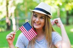 Menina com uma bandeira americana no quarto de julho Imagens de Stock Royalty Free