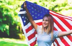 Menina com uma bandeira americana no quarto de julho Fotos de Stock Royalty Free