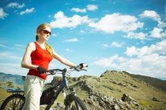 A menina com uma bicicleta de encontro às montanhas Fotos de Stock Royalty Free