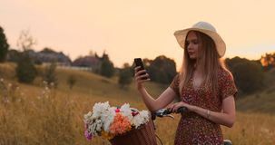 A menina com uma bicicleta em um chapéu faz um selfie usando um smartphone vídeos de arquivo