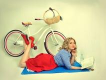 Menina com uma bicicleta em um estilo retro Foto de Stock