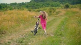 Menina com uma bicicleta na natureza video estoque