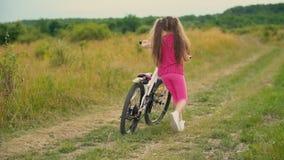 Menina com uma bicicleta na natureza vídeos de arquivo