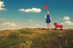 Menina com uma bola vermelha à disposição Imagens de Stock Royalty Free