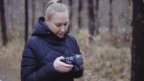 Menina com uma câmera à disposição o fotógrafo olha através das imagens tomadas floresta do outono, a primeira neve cinematic vídeos de arquivo