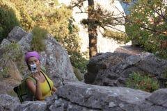 Menina com uma câmera entre rochas Imagens de Stock
