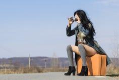Menina com uma câmera na estrada Fotografia de Stock Royalty Free