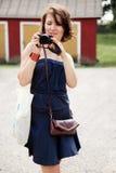 Menina com uma câmera que olha a foto Imagens de Stock Royalty Free
