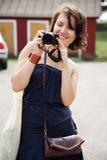 Menina com uma câmera que olha a foto e o sorriso Fotos de Stock