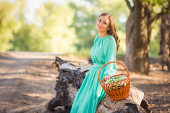 A menina com uma cesta em um vestido longo sentou-se para baixo para descansar em uma árvore caída velha imagem de stock royalty free