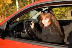 A menina com uma chave no carro vermelho Fotos de Stock Royalty Free