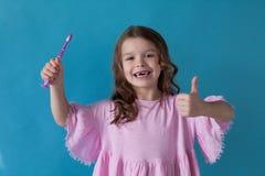 Menina com uma escova de dentes na odontologia agradável imagens de stock