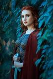 Menina com uma espada que está nos arbustos das uvas Imagem de Stock Royalty Free