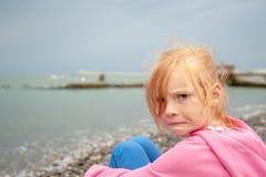 A menina com uma expressão facial desagradada na praia imagem de stock