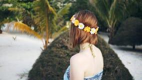 A menina com uma grinalda anda ao longo da praia video estoque