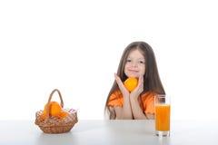 Menina com uma laranja na tabela Fotos de Stock