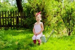Menina com uma lata molhando no jardim Foto de Stock Royalty Free