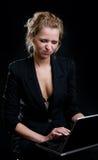Menina com uma lota que guarda um portátil em um preto fotografia de stock royalty free