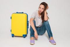 Menina com uma mala de viagem amarela Imagens de Stock Royalty Free