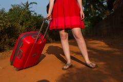 Menina com uma mala de viagem vermelha em uma estrada abandonada Começo da estação de turista chegada imagem de stock
