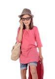 Menina com uma mala de viagem vermelha que fala no telefone Foto de Stock