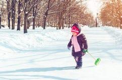 Menina com uma pá da neve que joga fora no inverno fotos de stock