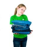 Menina com uma pilha das calças de brim Imagem de Stock Royalty Free