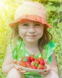 Menina com uma placa das morangos Fotos de Stock