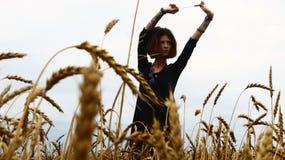 A menina com uma tatuagem em um campo da grão Fotos de Stock