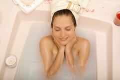 A menina com uma toalha em sua cabeça relaxa em um banheiro Imagens de Stock Royalty Free