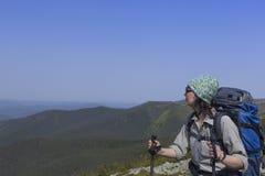 Menina com uma trouxa em uma caminhada da montanha no verão fotos de stock royalty free