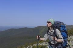 Menina com uma trouxa em uma caminhada da montanha no verão imagens de stock