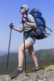 Menina com uma trouxa em uma caminhada da montanha no verão imagem de stock