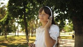A menina com uma trouxa vai estacionar nos fones de ouvido e escuta a m?sica e os sorrisos, adolescente acenam felizmente sua m?o video estoque
