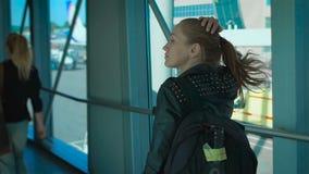 A menina com uma trouxa vai no corredor no aeroporto filme