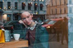 Menina com uma xícara de café que senta-se em um café fotos de stock royalty free