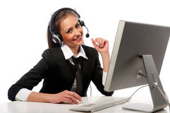 A menina com uns auriculares trabalha no computador Fotografia de Stock Royalty Free