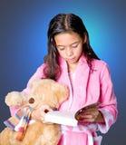 Menina com urso de peluche e storybook pronto para a cama fotos de stock royalty free