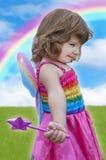 Menina com vestido feericamente e a varinha que estão sob um arco-íris colorido Fotografia de Stock Royalty Free