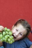 Menina com vestido que come as uvas brancas Imagem de Stock