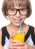 Menina com vidro do sumo de laranja Foto de Stock