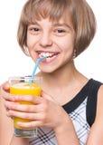 Menina com vidro do sumo de laranja Imagens de Stock