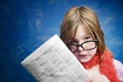 Menina com vidros e um jornal fotos de stock